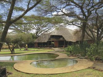 Blick durch den Garten zum strohgedeckten Haupthaus